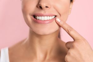 Young woman with healthy teeth on color background, closeup