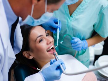 Her new dentist is not scary at all! Top view of dentist with his assistant examining his beautiful patient in dentist's office