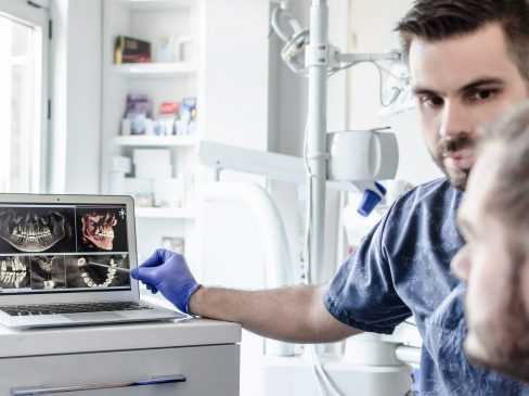Male dentist explaining dental x-ray to patient.