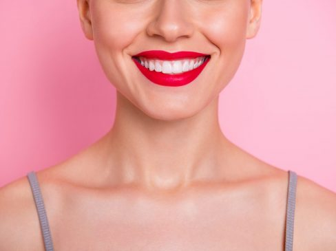 Close up cropped photo of cheerful girl visit dental medical clinic have implantology, procedure veneers enjoy her teeth strong white fresh breathing isolated over pink color background
